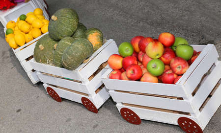 small train full of fruit with apples and pumpkins