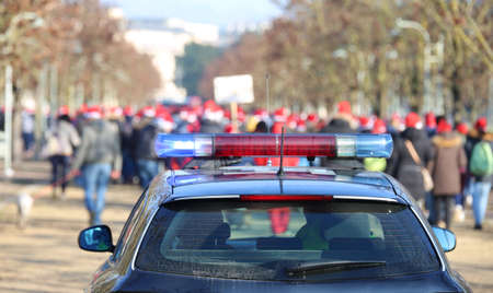 Photo for police car during the manifestation with many people in the public park - Royalty Free Image