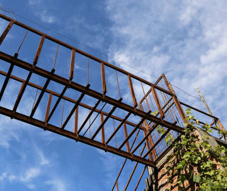 ancient suspended bridge of rusted iron outdoors and blue sky and clouds