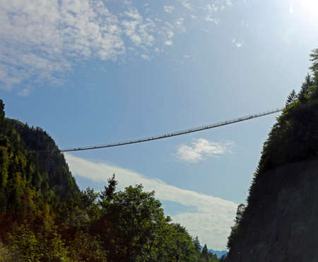 very long suspension bridge between two mountains with many adventurous intrepid people crossing it