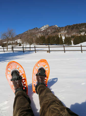 two legs with corduroy pants and orange snowshoes in mountains