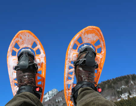 two orange snowshoes in winter and blue sky on background