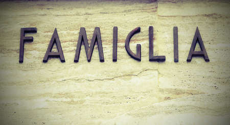 Foto per big text FAMIGLIA that means famiyl in Italy Language with copy space and old vintage effect - Immagine Royalty Free