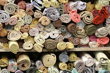 dozens of rolls of precious fabrics on the shelves of the haberdashery