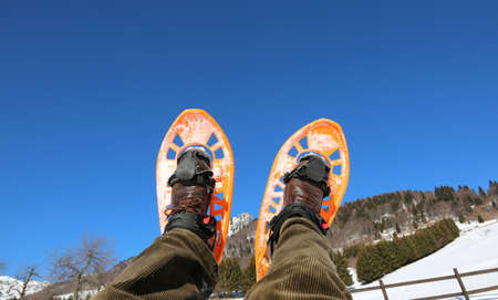 snowshoes raised to the sky behind a beautiful landscape