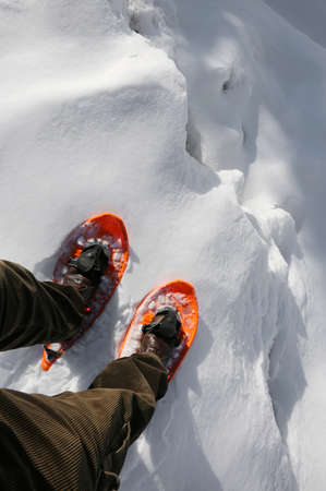 Reckless hiker with orange snowshoes and velvet pants on the edge of a crevasse in the glacier in the mountains