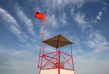 Lifeguard watchtower on the beach with the big red flag waving in the wind