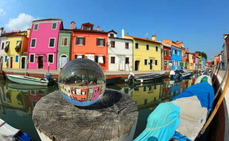 colorful houses on the island of Burano near Venice in Italy and a large glass sphere with the reflection of the village