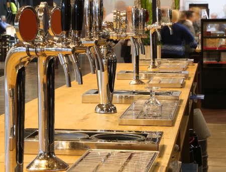 Foto de many draft beer taps on the counter of an Irish pub - Imagen libre de derechos