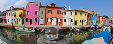 Colored houses in Burano Island near Venice photographed by fisheye lens and a glass globe