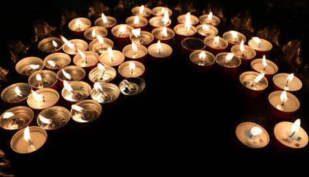 many candles lit by the faithful illuminate a dark church