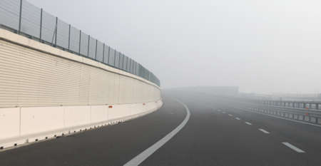 very dangerous thick fog near the sharp curve of the highway in winter