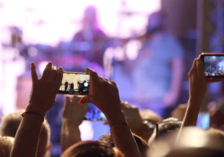Photo pour many people at live concert with smartphones near the stage - image libre de droit