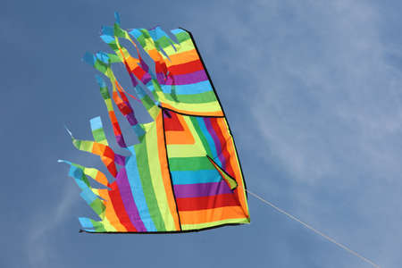 Vivid colors of a big kite flying on the blue sky