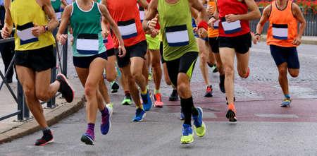Foto de group of athletes runninng on the road during a footrace - Imagen libre de derechos