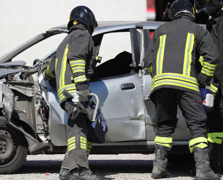 Photo pour team of firefighters opens the damaged car after the road accident - image libre de droit
