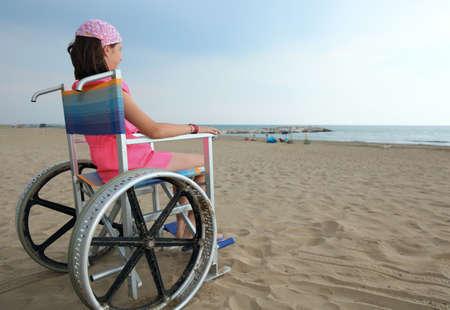 Foto de disabled boy sitting in a wheelchair look at the sea from the beach - Imagen libre de derechos