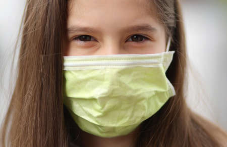 young girl with long brown hair wears a surgical mask to protect herself from the terrible and contagious Corona Virus