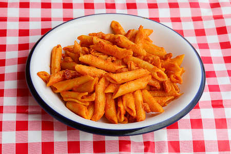 seasoned pasta with tomato and cheese on a red and white checkered tablecloth in the Italian restaurant