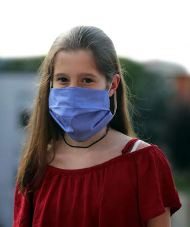 Beautiful young girl with long hair and blue surgeon mask during the lockdown caused by the deadly Coronavirus also called Covid-19