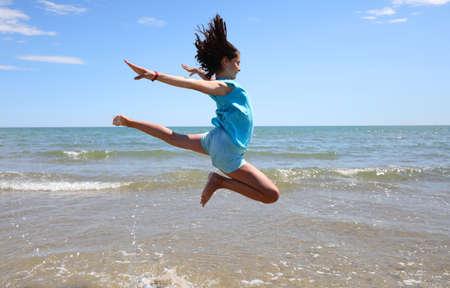 Foto de athletic girl takes an amazing jump over the sea on the shore of the beach in summer - Imagen libre de derechos