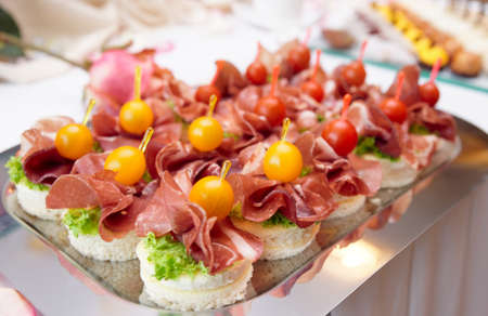 Canapes with cured ham (jamon or prosciutto) on banquet table