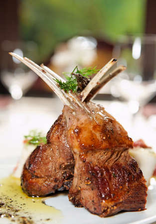 Raw rack of lamb fried with aromatic olive oil, herbs and spices