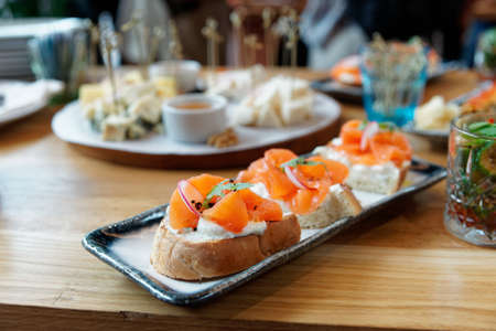 Foto de Smoked salmon, radish and creamy cheese on bread, set of bruschettas, catering event - Imagen libre de derechos