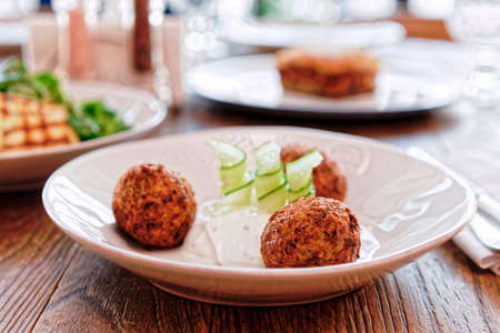 Photo pour Zucchini croquettes and other dishes on restaurant table, Greek food, toned - image libre de droit