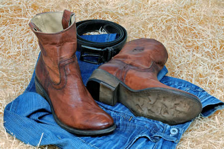 Pair of traditional brown leather cowboy boots and blue jeans and leather brown belt curtailed into a ring on straw