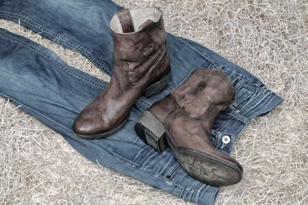 Pair of traditional leather cowboy boots and jeans on straw. Retro and dark toning of the image