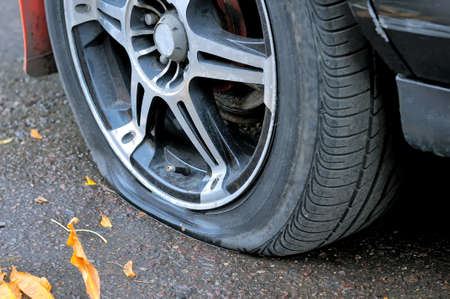Photo pour Flat tire of a car on the pavement. Side view close up - image libre de droit