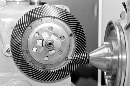 Industrial machine with a conical gear and a circular gear, cogwheel with spiral machine teeth. Black and white toned image