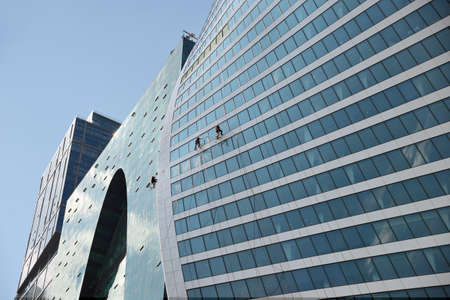 Photo pour Moscow, Russia - May 28, 2019:  Industrial climbers washes glass on the facade of a skyscraper in the business district called Moscow City - image libre de droit