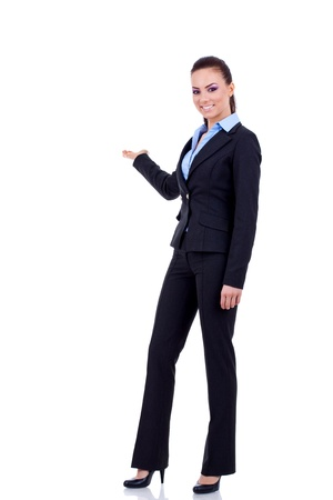 Business woman points at something in her back. Isolated on white background