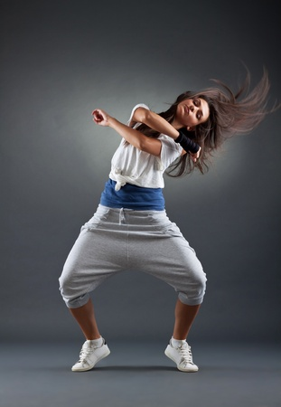 young female dancing on the grey background, studio shot