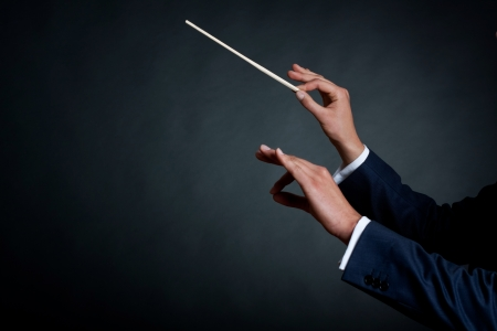 Foto de image of a male orchestra conductor directing with his baton in concert  - Imagen libre de derechos