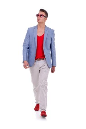 Stylish young man walking on white background
