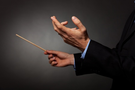 Cropped image of a male music conductor directing with his baton in concert