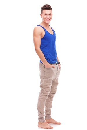 barefoot sexy young man standing with his hands in his pockets on white background