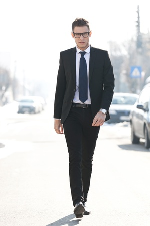young confident business man walking towards the camera - outdoor picture