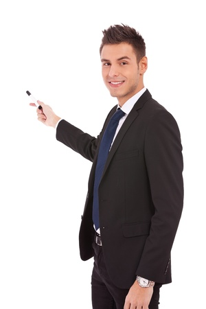 handsome young business man in a suit pointing with a pen on white background