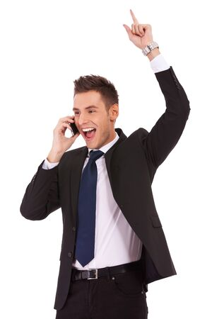 screaming young business man discussing on a cell phoneand winning, isolated on white background