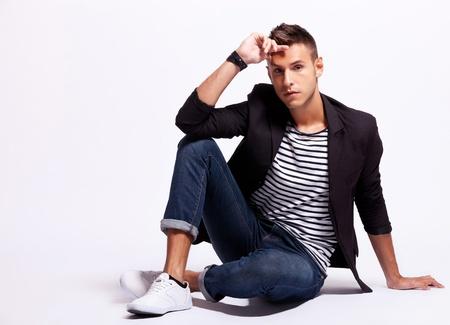 Foto de fashion male model looking serious while sitting on a gray background - Imagen libre de derechos