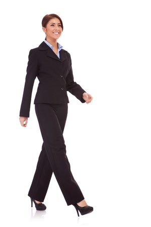 full body picture of a business woman walking isolated over a white background の写真素材