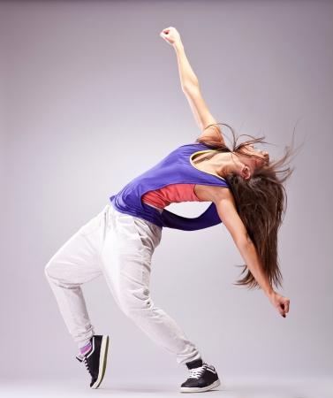 Beautiful woman dancer in hip hop attire striking a pose