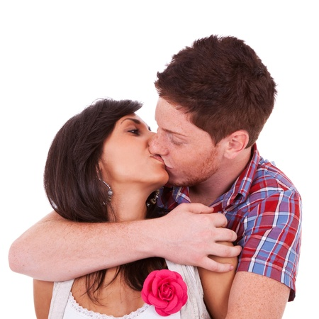 A portrait of a young couple kissing, over white background