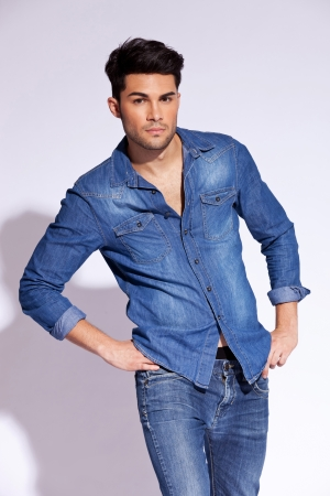 Young male model wearing a casual jeans shirt  posing in the studio