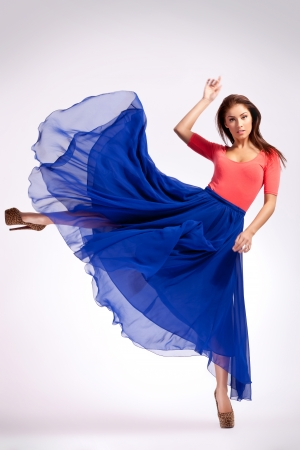 Foto de young woman in blue dress kicking to her side and looking at the camera - Imagen libre de derechos