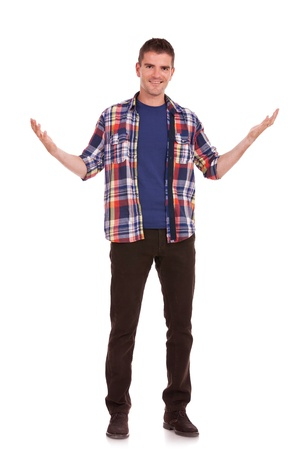 Full length picture of a young casual man welcoming you on white background